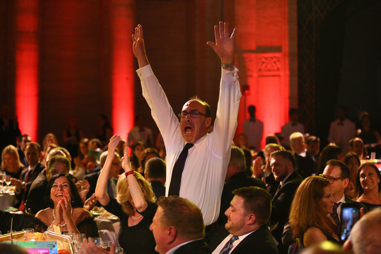 Man standing celebrating auction win.